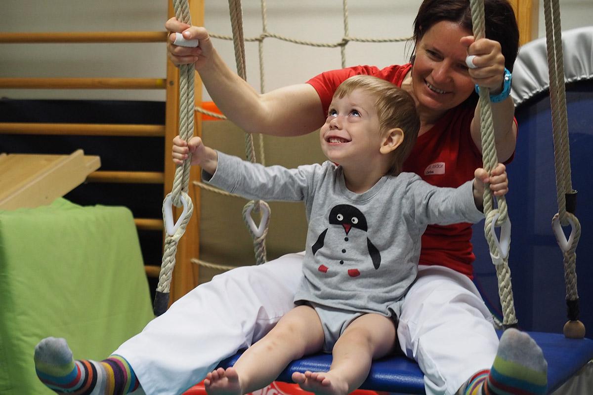 Kind und Therapeutin auf Schaukel